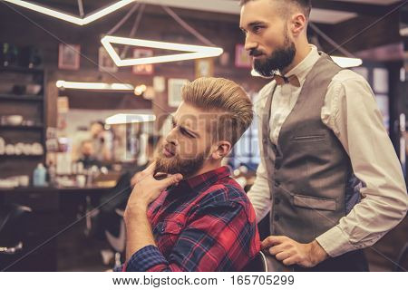 Handsome bearded man is rubbing his chin after getting haircut by hairdresser at the barbershop