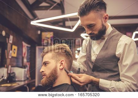 Side view of handsome bearded man getting haircut by hairdresser at the barbershop