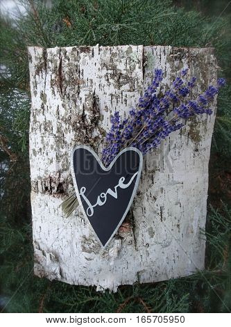A black and silver heart with the word, Love, written in cursive, forms the center of this natural outdoor arrangement with lavender and birch bark in the background.  Vertical.