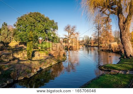 Panoramic picture of a small lake and public footpath  in Regents Park, London