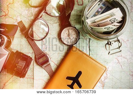 Wanderlust And Adventure Concept, Jar With Money For Travel Compass Camera Passport Glasses On Map,