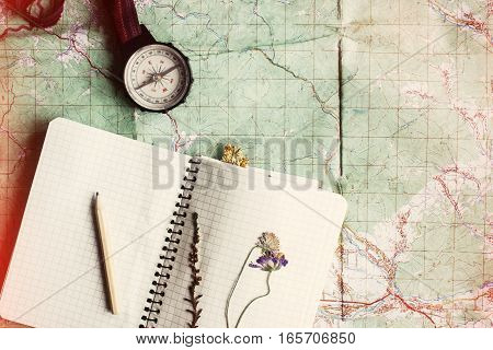 Wanderlust And Adventure Concept, Compass And Notebook With Wildflowers And Pencil On Map, Top View,