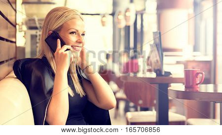 Beautiful young woman talking on the phone cup of tea coffee fashion city breakfast restaurant business woman discussion resting looking out the window