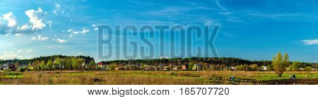 Panorama of typical Ukrainian rural landscape in spring. Agricultural fields and the town on the horizon, Irpin, Ukraine. Farmers working on farm land.