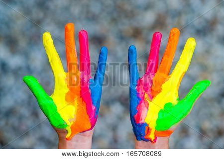 Hands painted in colorful paints ready for hand prints - very shallow depth of field - only hands are sharp