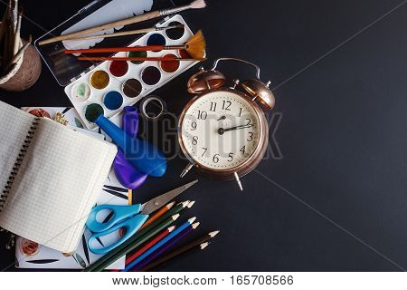Back To School Concept, Colorful Pencils Paints Brushes Scissors And Notebook With Old Clock On Chal