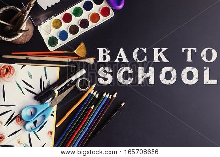 Back To School Concept Text White Chalk On Black Board, Colorful Pencils Paints Brushes Scissors And
