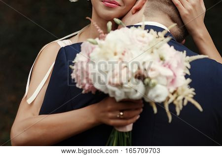 groom kissing bride at neck luxury wedding couple hugging tender romantic moment at garden with pink blossoms