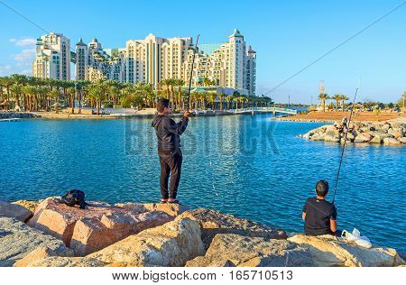 EILAT ISRAEL - FEBRUARY 24 2016: The stone pier is the best place for fishing enjoying the views of resort on February 24 in Eilat.