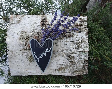 A black heart with the word, Love, written in silver calligraphy, lavender flowers, and birchbark create an artistic natural outdoor arrangement.  Horizontal, copy space.