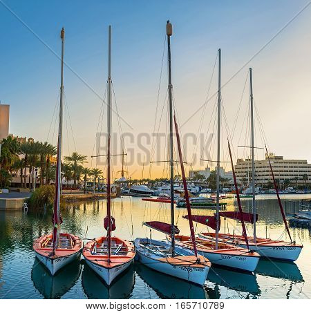 EILAT ISRAEL - FEBRUARY 23 2016: The small sailing yachts in Lagoona in bright sunset lights on February 23 in Eilat.