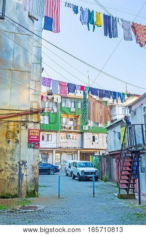 BATUMI GEORGIA - MAY 25 2016: The old residential houses in the city center with car parkings and drying clothes on May 25 in Batumi Georgia.