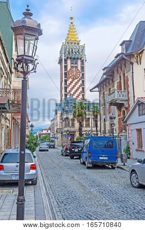 BATUMI GEORGIA - MAY 24 2016: The narrow street of the old town with the modern clock tower of Piazza hotel on the background on May 24 in Batumi.