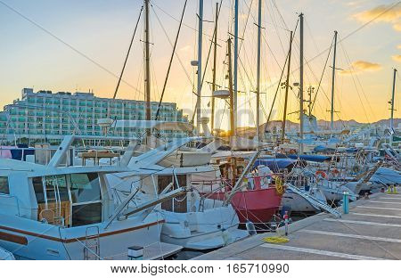 The bright sunset sky behind the masts of yachts in port of Eilat Israel.