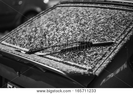 Wiper and windscreen of the parked car covered with snow. clouse up