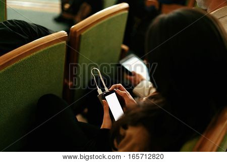 Stylish Woman Holding Phone With Empty White Screen And Power Bank, Sitting At Meeting, Business Mar