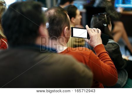 Stylish Man Holding Phone With Empty White Screen In Audience And Recording, Sitting At Meeting, Bus