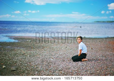 A young girl with short hair in a white blouse and black pants is sitting on his knees on the beach on the background of beautiful blue sky.