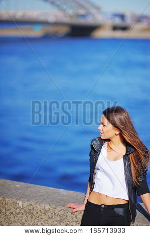 Portrait profile of young beautiful woman with tousled in the wind long hair standing on the waterfront on the background the blue waters of the Neva.