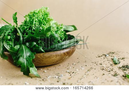 Delicious Fresh Salad Arugula Spinach In Wooden Bowl  On Craft Background, Space For Text
