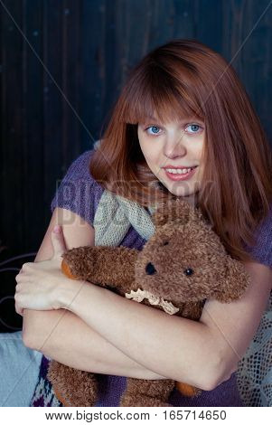 Young girl hugging a toy teddy bear. The toy in his hands.
