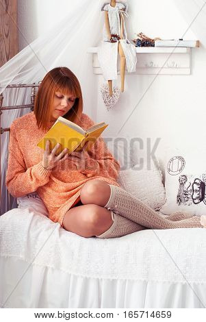 Girl with the book in the interior. Young woman reading.