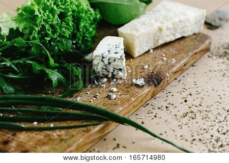 Delicious Fresh Salad Arugula Spinach And Parmezan And Gorgonzola Cheese On Wooden Cooking Board