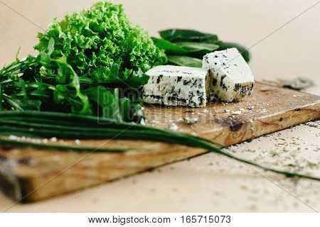 Delicious Fresh Salad Arugula Spinach And Gorgonzola Cheese On Wooden Cooking Board