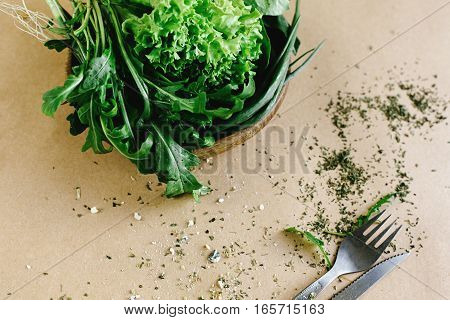 Delicious Fresh Salad Arugula Spinach In Wooden Bowl And Cutlery On Craft Background