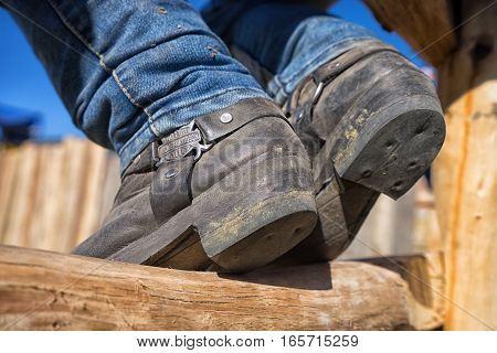 August 13 2016 Ibarra Ecuador: closeup of a boot of a cowboy sitting on the fence during a rodeo in La Esperanza