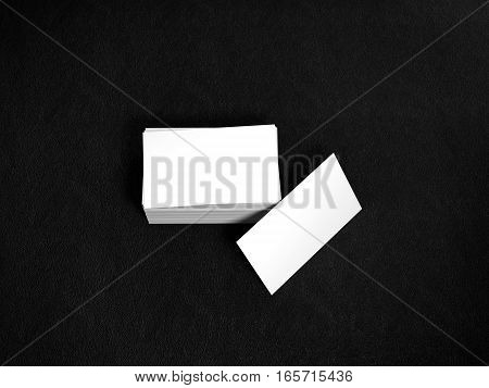 Stack of white business cards. Name cards mockup template on black leather background. 3D Rendering with shadow