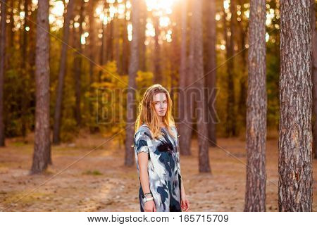 Happy girl smiling in the woods at sunset. Woman and bokeh.