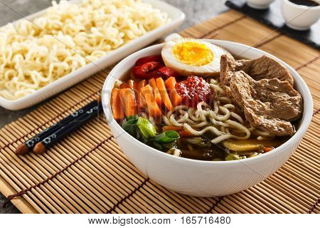 Shoyu ramen noodle soup with veggies ginger and soy meat.