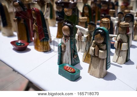 August 8, 2016 Otavalo, Ecuador: small wooden statues closeup in the indigenous artisan market