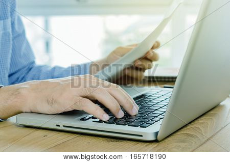 Close-up Man Hand Using Computer Laptop And Finance Document.