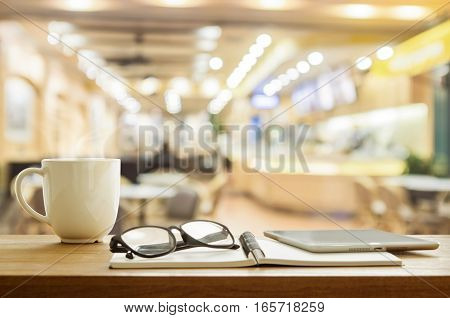 Cup of coffee and tablet on wooden table in coffee shop selective focus. Vintage filter