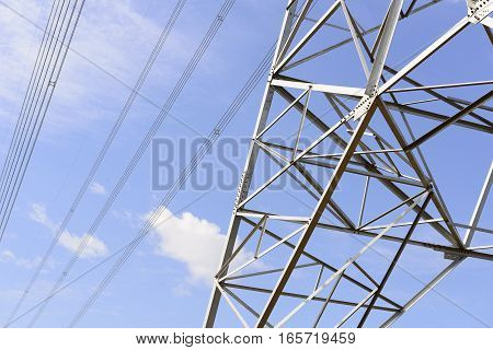 Closeup of the base structure of electricity pylon with the blue sky