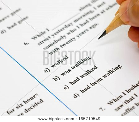 closeup english exam sheet with hand holding pencil