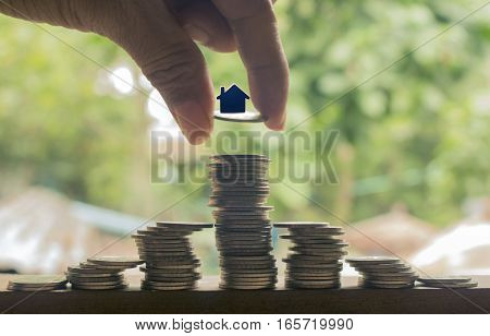 hand stacking of coins with house model concept idea for save money and business.