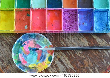 paint brush and oil color in plastic tray on wooden board