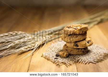 Chocolate cookies on a cloth sack on wood. Chocolate chip cookies and rice malt shot on a brown cloth .