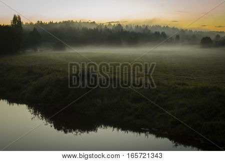 Sunrise On The Field With Fog Near The River Bank