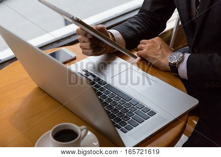 businessman working with digital tablet computer and smart phone and laptop with financial business strategy layer effect on wooden desk as concept.