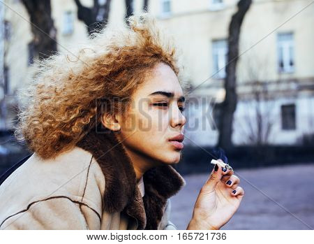 young pretty girl teenage outside smoking cigarette close up, looking like real junky, social issues concept casual
