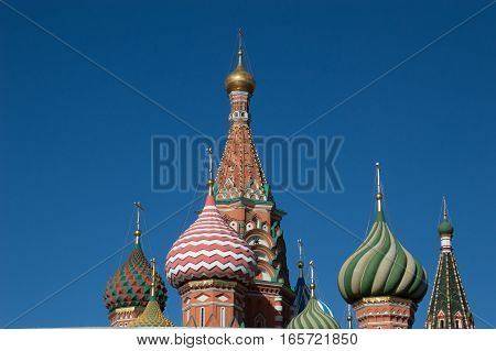 The colorful onion domes of St. Basil's Cathedral topped with Orthodox crosses against a deep blue sky. Located on Red Square in Moscow Russia.