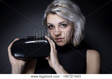 Woman holding a virtual reality headset used in VR movies or video games. The gadget is wearable technology for leisure. She is advertising the non branded generic device.