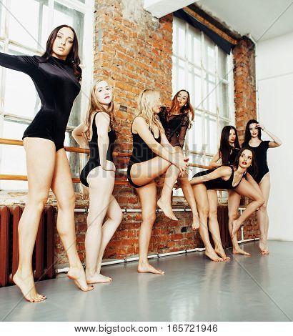 Many girls training in studio ballet, long woman legs   bracing, wearing   black bodysuit, lifestyle real people concept