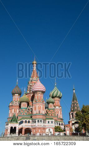 St. Basil's Cathedral, a Russian Orthodox Church on Red Square, Moscow, with its ornate design and colorful onion domes topped with crosses. Deep blue sky is above.