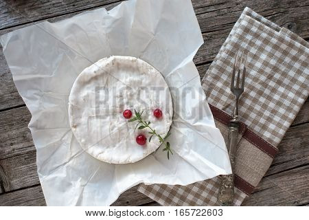 Camembert cheese on piece of paper decorated with redcurrants and thyme.