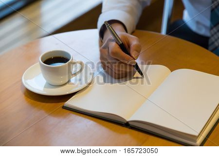man notebook with pen and coffee on old wooden table.